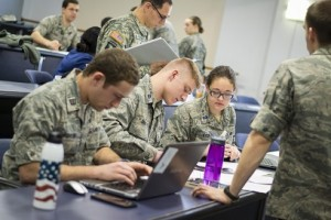 WPI Air Force ROTC cadets Miles Schuler, Brian Gasco and Brittany Kyer plan a solution to a hypothetical cyber threat during the exercise, while U.S. Army Maj. Francisco Escobar, assistant professor of military science, reviews a data folder related to the lab.