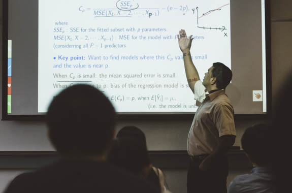 Math professor teaching statistics on projector