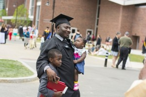 A proud graduate poses for photos with young family members.