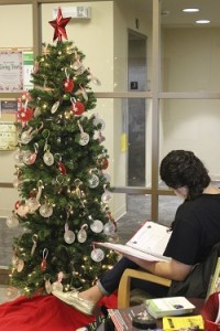 A student looks through one of the binders listing the children requesting gifts through WPI's Giving Tree holiday program.