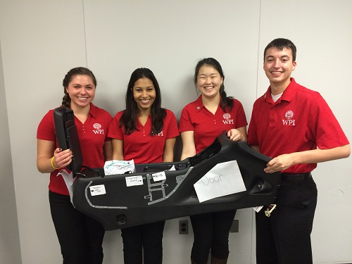 WPI students Kate Piotrowicz, Michelle Acevedo, Dulguun Gantulga and Keith Guay hold up a prototype of a BMW center car console they designed for the competition.