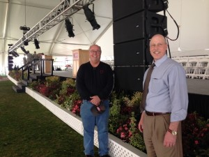 Terry Pellerin and Greg Snoddy stand near the front of the stage as lighting and sound equipment are installed.