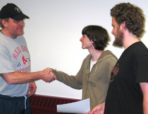 Red Sox pitcher Curt Schilling, founder of the Maynard, Mass.-based video development company 38 Studios, congratulates WPI first-year students Morgan Quirk and Andrew Tremblay for their video game creation Super Munch 2 Turbo.