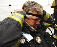 A Worcester firefighter dons an early prototype physiological sensor developed at WPI during a simulated rescue mission.