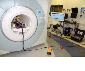 From left, the robot inside the MRI unit; the foot pedal used to activate the robot; a screen that displays its status, and (on floor) the robot controller.