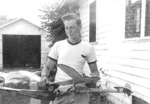 Noiles at his family home in Hudson, Mass., with a model airplane he constructed.