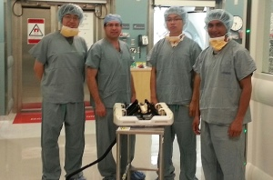 Fischer, second from left, and, from left, PhD candidates Weijian Shang, Gang Li, and Nirav Patel, with the MRI-compatible robot.