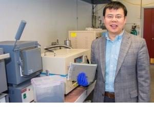 Yan Wang holds a lithium-ion battery cell used in electric vehicles. His process breaks down the batteries to produce the powder shown to the left. New cathode materials can be made from this powder.