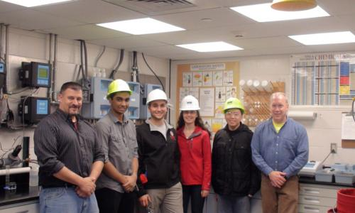 Four WPI students wearing hard hats pose with two project center sponsors in a lab area.