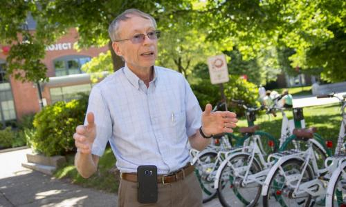 John Orr stands in front of green and white bicycles and trees that are out of focus. He's got gray hair and is wearing glasses, dark khaki pants, and a light blue checkered button-down shirt. A black cell phone case is clipped to his belt.