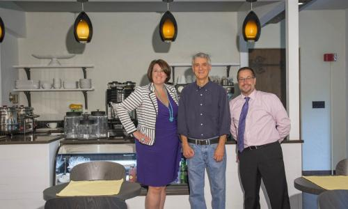 Emily Perlow, Mark Richman, and Joe Kraskouskas in front of the counter at the Quorum. They're all smiling.