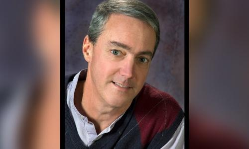 Steve Taylor smiles at the camera with a gray background. He's got gray hair and is wearing a light-colored button-up shirt and a red and blue pullover vest.