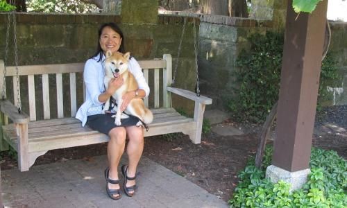 Kathy Chen sits on a wooden swing in the Higgins gardens. She is smiling and holding a dog in her lap. She's wearing a black skirt and sandals, and a light shirt and blazer.