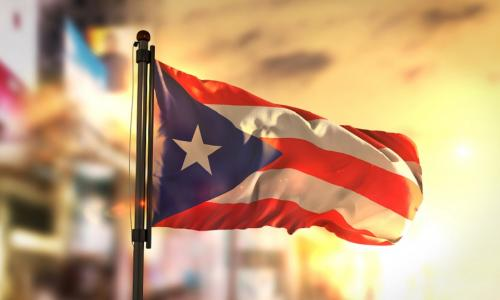 A photo of the Puerto Rican flag with yellow and orange sunshine in the background, looking as if it was taken at sunset or sunrise.