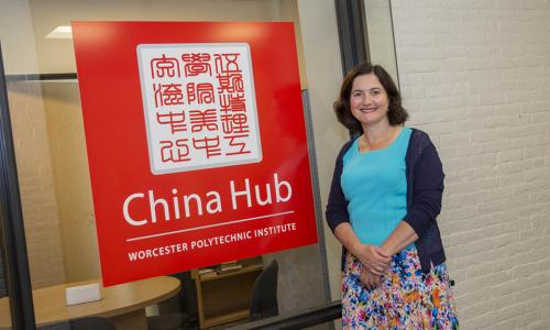 Jennifer Rudolph stands next to a bright red and white China Hub sign. She is smiling, and wearing a colorful dress.