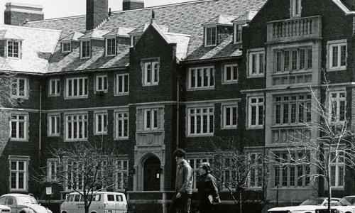 A black and white photo of Sanford Riley Hall, with two students walking in front of it. Several old cars are parked along the front of the building.