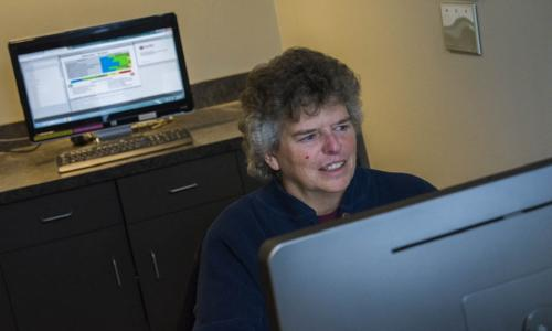 Beth Wilson studies a computer screen, with another screen behind her. She has gray hair, and is wearing a dark blue sweater and red shirt.
