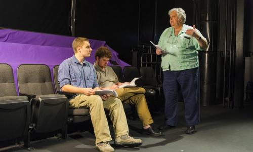 Mike Ciaraldi (right) discusses a scene in the Little Theatre with two male students who are seated in theatre chairs. They're all holding scripts; Ciaraldi is talking, one student is looking at him, and one is looking at the script.