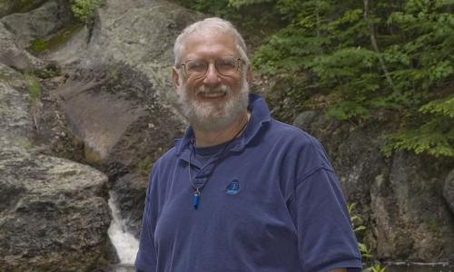 Roger Gottlieb stands in front of rocks and foliage in a nature setting. He is smiling, has white hair and a beard, and is wearing glasses and a blue polo shirt.