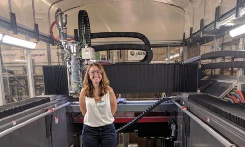 Amy Peterson stands inside of a large 3D printer. She is smiling and wearing safety glasses, a white blouse, and blue-and-white polka dot pants.
