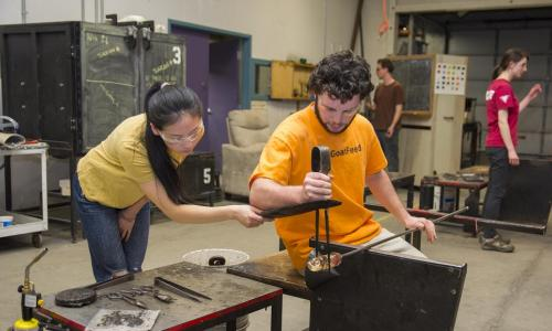 Two students participate in a glassblowing class. A male student in an orange shirt is holding a pole with a piece of glass on the end, while a female student in a yellow shirt uses a tool to hold the glass steady.