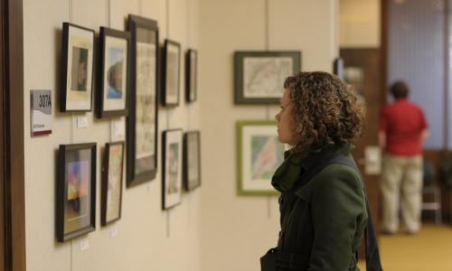 In a shot from the side, a woman in a green sweater looks at some art on display in the Gordon Library.
