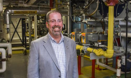 "Eric Beattie stands in an equipment room with pipes and a ""high pressure steam"" sign behind him. He's smiling and is wearing safety glasses, earplugs, a gray suit jacket, and a blue and white checkered shirt."