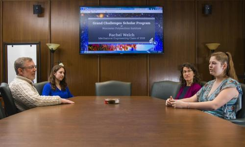 "Two faculty members sit across a conference table from two students, with a computer screen projected in between them that reads, ""Grand Challenges Scholar Program of Worcester Polytechnic Institute."" alt"