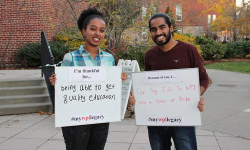"""Two students smile while holding up signs that read: """"I'm thankful for being able to get a quality education"""" and """"Because of you, I can say I go to WPI with a sense of pride."""""""