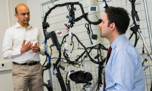 Raghvendra Cowlagi, left, and Alexander Wyglinski, in the MITRE-WPI Collaboratory. Behind them is the wiring harness for a 2014 Chevy Impala, used for projects on autonomous vehicle security. alt