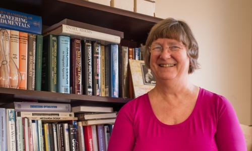 Holly Ault stands in front of a full bookshelf. She's smiling, and is wearing a pink shirt and glasses.