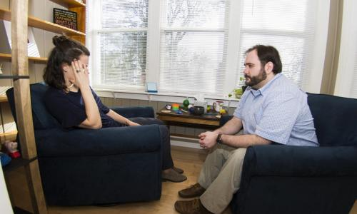 A counselor sits across from a student during an appointment. They're both in plush navy blue chairs, with three windows with blinds behind them.