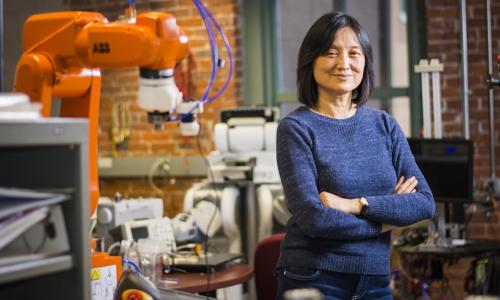 Jing Xiao stands in a robotics lab with a brick wall and several different machines and robots behind her. She has black hair, is smiling, has her arms crossed, and is wearing a blue sweater and jeans.
