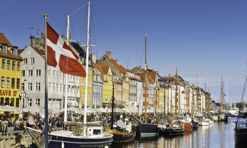 A photo of a river in Copenhagen lined with boats. Colorful homes also line the river behind the boats.