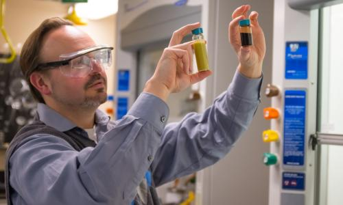 Professor Timko holds up and examines two vials, a large one on the left containing a yellowish liquid and a smaller on on the right containing a dark brown liquid alt