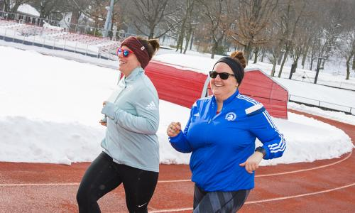 Meredith Merchant and Jessica Karner run along the WPI track together. They're both smiling, dressed in workout clothes, and are wearing sunglasses.