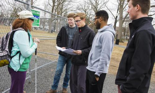 Four WPI students meet with a woman in front of a fence at Elm Park. One student is holding a map or blueprints while the rest look on.