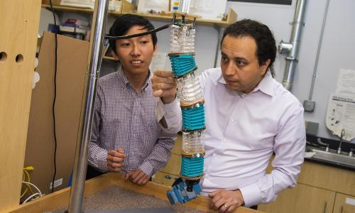 WPI professor Cagdas Onal (right) and PhD candidate Junius Santoso examine a soft manipulator robot in the Soft Robotics lab at WPI. alt