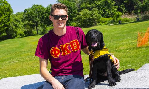Jake Scheide sits in Institute Park with Diesel by his side. He's smiling and wearing a red fraternity shirt and sunglasses. Diesel's tongue is out, he has black fur, and is wearing his yellow training cape.
