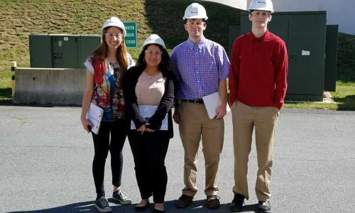 Four students wearing white hard hats and protective glasses and three carrying clipboards smile together at their project site in Boston, Mass.