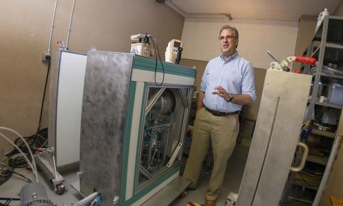 WPI professor David Medich stands next to the neutron generator he is developing for medical imaging. alt