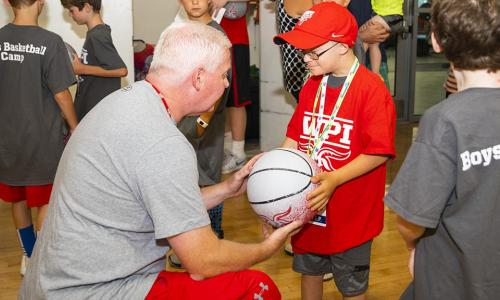 """Fist Bump Kid"" Liam Fitzgerald accepts a basketball from a member of the WPI basketball coaching staff. alt"
