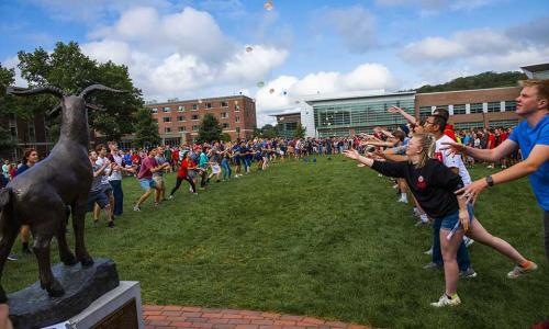 New students participate in a water balloon toss on the Quad in front of the proud goat Gompei statue.
