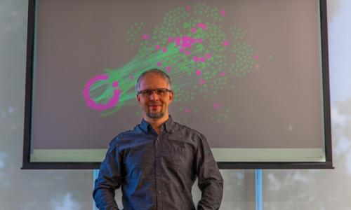 Dmitry Korkin stands before a depiction of a network of proteins that are affected by type 2 diabetes (in pink). The lines represent protein-protein interactions that are expected to affected by the mutations that are linked to types 2 diabetes. alt