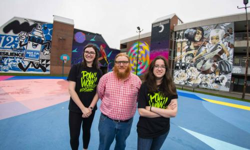 Sarah Kwatinetz, Joseph Cullon, and Brittany Goldstein stand in front of two of the many murals now decorating Worcester as part of Pow! Wow! Worcester. alt