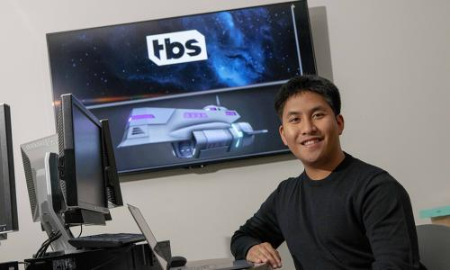 Joshua Galang smiles in front of a projection screen showing a model of an animation from Final Space, as well as the Final Space logo, with his laptop in front of him.