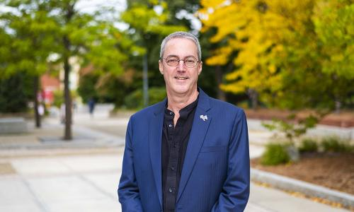 Steve Taylor smiles on campus. He's wearing glasses, a dark blue suit jacket, black shirt, and Gompei pin. Yellow and green trees are behind him.