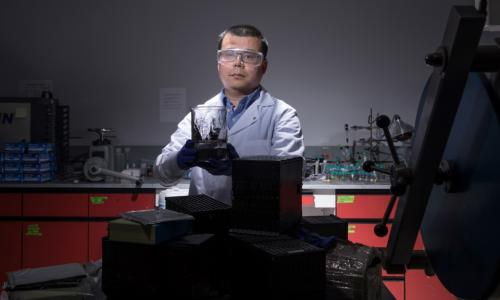 Yan Wang in his lab at WPI with a sample of the cathode materials he is able to produce with his process for recycling lithium-ion batteries. The focus of his work with USABC is electric and hybrid vehicles batteries, like those piled on the lab table. alt