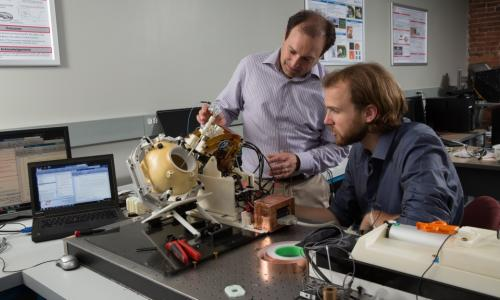 Gregory Fischer, left, and research scientist Christopher Nycz examine a prototype of the MRI-compatible robotic system developed in the first phase of the NIH-funded research program. alt