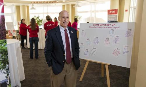 "Greg Snoddy stands in the Rubin Campus Center next to a poster board that says ""Giving Day is Nov. 27! What does 'giving back' mean to you?"""